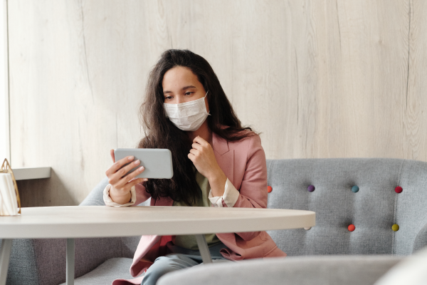 Woman with face mask holding and watching smartphone